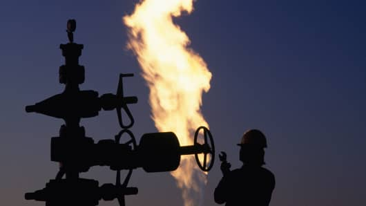 Natural gas pipe and worker with fire silhouetted