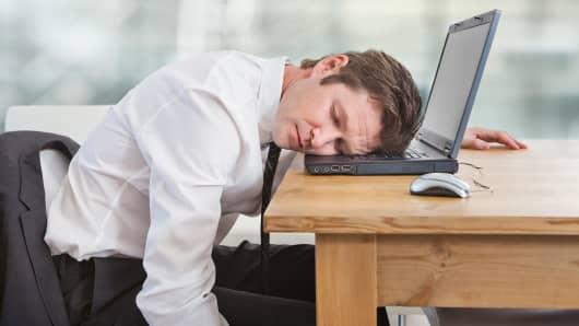 Employee asleep at work on his laptop