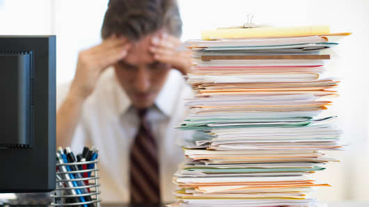Stressed out businessman at desk with stack of paper