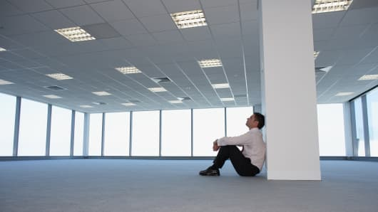 Man in empty office sitting against a column