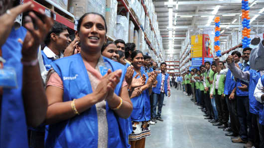 Indian employees welcome Bharti Wal-Mart President Managing Director and CEO Raj Jain (unseen) following an inauguration ceremony of a newly opened Bharti Wal-Mart Best Price Modern wholesale store in Hyderabad on September 26, 2012.