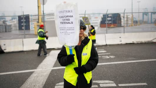 Members of International Longshore and Warehouse Union Local 63 Office Clerical Unit walk a picket line near APM Terminals, halting cargo at the busiest seaport complex in the nation.