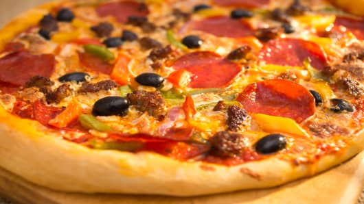 Pizza with sausage, pepperoni, bell peppers, cheese and olives.