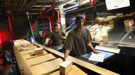 Workers sort packages at the FedEx Ground hub in Chicago.