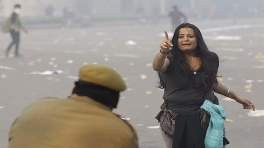 A woman protester pleads as a police person fired a tear gas shell during a protest against the Indian government's reaction to a recent gang rape.