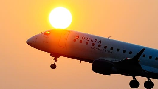 A Delta airline's aircraft takes off from the Ronald Reagan National airport as the sun rises in Washington, DC.