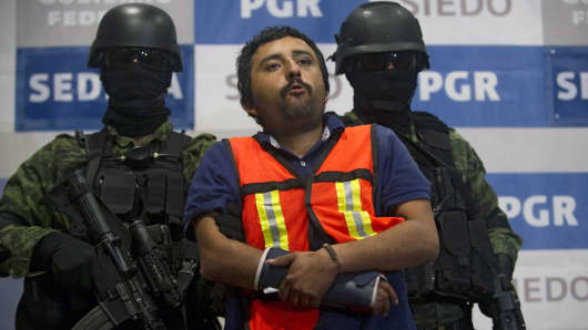 Mexican Army soldiers escort Luis Jesus Sarabia Ramon (C), aka 'El Pepito' or 'Z-44', an alleged leader of Los Zetas drug cartel, during his presentation to the press on January 13, 2012 in Mexico City.
