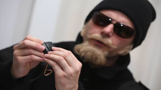 Thomas Kuban, who for over a decade filmed neo-Nazi concerts and other right-wing events, wears a disguise as he explains the use of one of the miniature cameras he used.