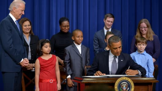 President Obama signs executive actions to curb gun violence as Vice President Joe Biden (L) and invited guests look on.