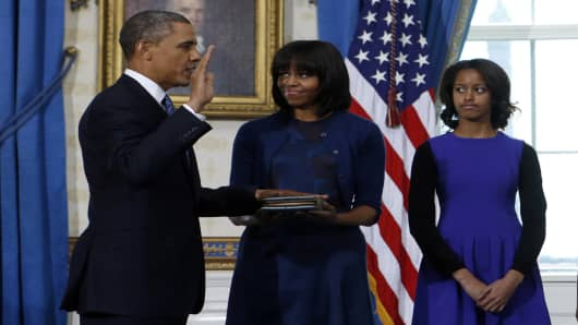 U.S. President Barack Obama (L) takes the oath of office from U.S. Supreme Court Chief Justice John Roberts as first lady Michelle Obama holds the bible with their daughter Malia at right in the Blue Room of the White House in Washington, January 20, 2013.