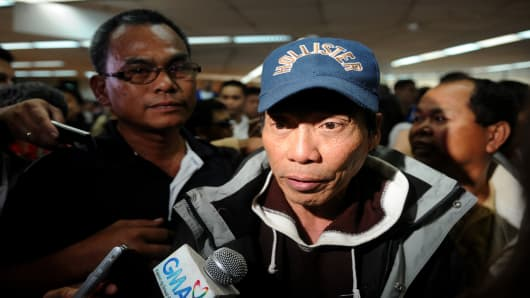 A Filipino overseas worker (R) is interviewed by the press upon his arrival at Manila International Airport on January 20, 2013