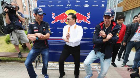 Korean rapper Psy (C) teaches Red Bull Racing drivers Mark Webber (L) and Sebastian Vettel (R) the Gangnam Style dance before the Korean Formula One Grand Prix at the Korea International Circuit on October 14, 2012 in Yeongam-gun, South Korea.