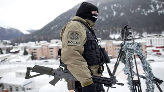 A police officer stands guard next to a sniper rifle atop the Congress Centre, venue of the World Economic Forum