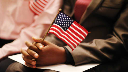 A petitioner holds a US flag during a naturalization ceremony.