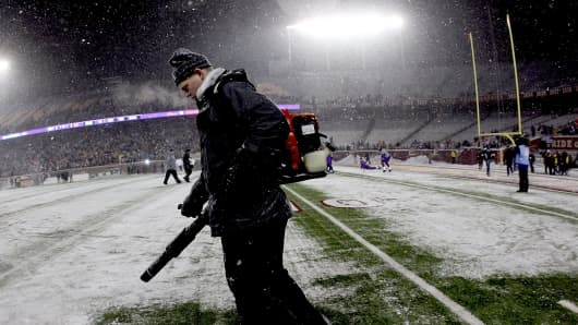 Workers clear snow from the field before Minnesota Vikings play the Chicago Bears at TCF Bank Stadium on December 20, 2010 in Minneapolis, Minnesota.