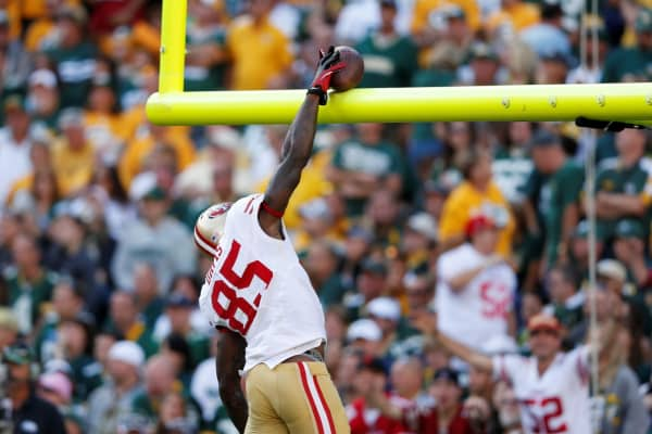 Vernon Davis of the San Francisco 49ers dunks the football over the goal post after catching a touchdown pass in the game against the Green Bay Packers at Lambeau Field on September 9, 2012.