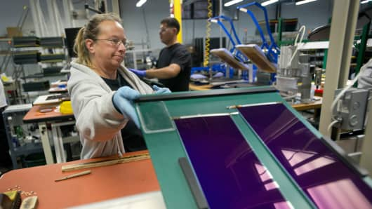 An employee stacks mini solar cells after ends are soldered on them at the Xunlight Corp. factory in Toledo, Ohio, U.S.