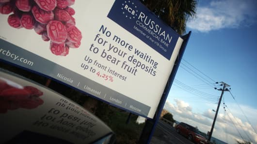 A car drives past a billboard promoting a Russian bank on a main road in the southern Cypriot port of Limassol.