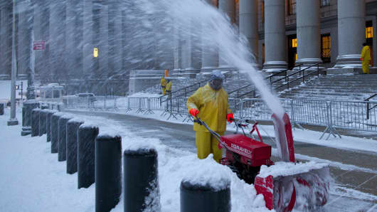 A city employee clears snow from the sidewalk at the United States Court following a major winter storm on February 9, 2013.