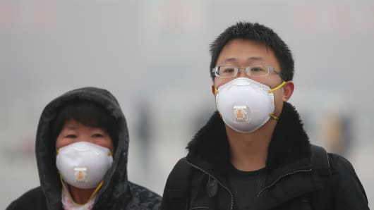 Tourists wearing the masks walk on the Tiananmen Square during severe pollution on January 31, 2013 in Beijing, China.