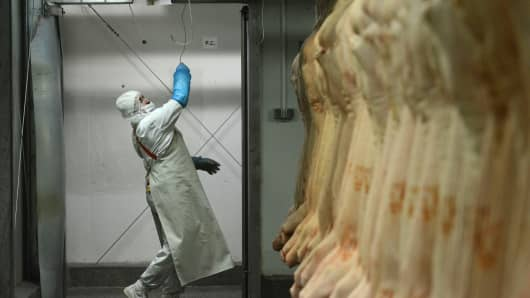 A worker processes pork at 'DOLY-COM' abattoir, one of the two Romanian companies exporting horse meat to EU countries.