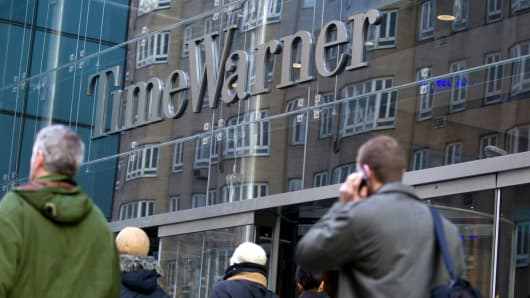 Pedestrians walk past the Time Warner Center, headquarters building of Time Warner Inc., in New York, U.S.