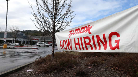 A sign advertising jobs is posted in fromt of a TJ Maxx store in San Rafael, California.