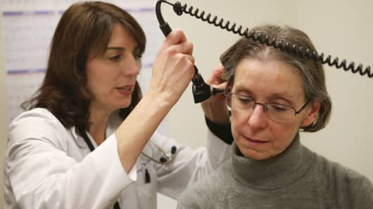 A doctor checks a patient who is experiencing flu symptoms.