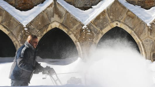 A man clears snow in front of a church in Boston, Mass.