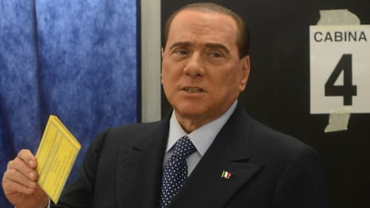 Italian former Prime Minister Silvio Berlusconi casts his ballot at a polling station on February 24, 2013 in Milan.