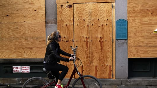 A woman rides by a closed business affected by Super Storm Sandy in the heavily damaged South Street Seaport.