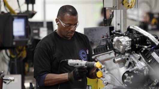 An employee assembles an 2.0 liter ecoboost engine on the production line at the Ford Motor Co. Cleveland Engine Plant in Brook Park, Ohio, U.S