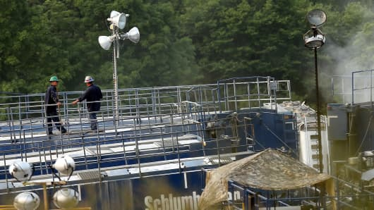Men work on a natural gas valve at a hydraulic fracturing site in South Montrose, Pa.