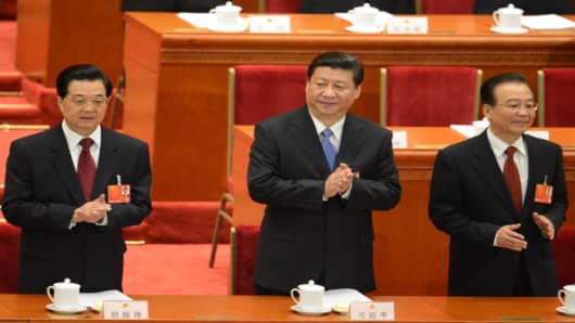 Chinese President Hu Jintao, Vice President Xi Jinping and Premier Wen Jiabao applaud during the opening session of the Chinese National People's Congress (NPC) at the Great Hall of the People in Beijing on March 5, 2013
