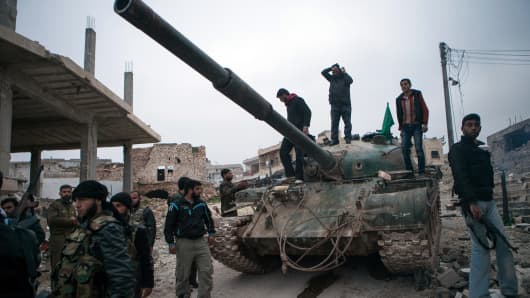 Syrian rebels gather around a T-72 tank, captured from government forces, in the flashpoint Syrian province of Idlib near the border with Turkey.