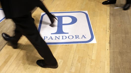 Traders on the floor of the New York Stock Exchange walk past the Pandora Media logo on its first day of trading as a public company.