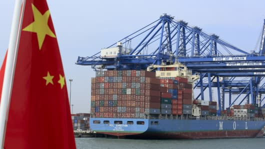 A Chinese flag flies on a vessel moving past shipping containers being unloaded at a Tianjin Port Group Co. dock in Tianjin, China.