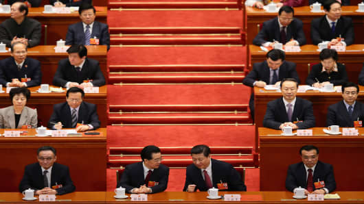 China's newly-elected President Xi Jinping (R) talks with former President Hu Jintao (L) during the fourth plenary meeting of the National People's Congress at the Great Hall of the People in Beijing.