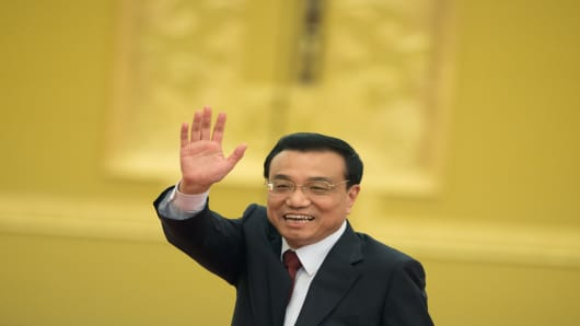 New Chinese Premier Li Keqiang waves as he leaves his first press conference after the closing session of the National People's Congress  at the Great Hall of the People in Beijing on March 17, 2013