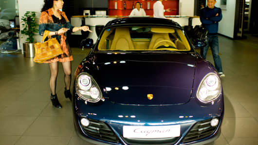 Chinese consumers select a car at a Porsche dealership in Shanghai.