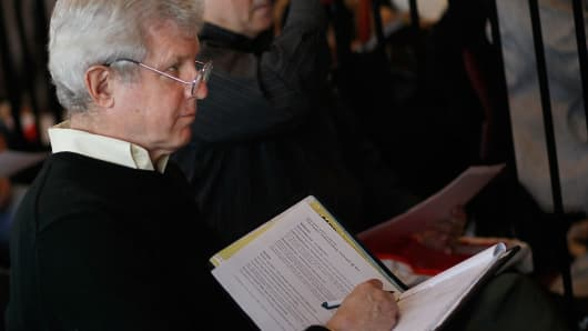 An older job-seeker takes notes during an employment seminar in New York.