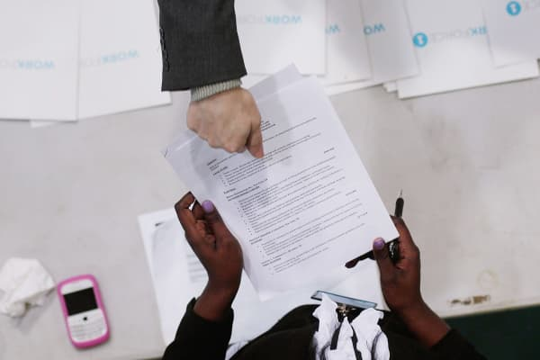 A job-seeker (top) hands his resume to Candice Perkins, a representative of Workforce1 during a 'Work Search' event aimed at older unemployed people in New York City.