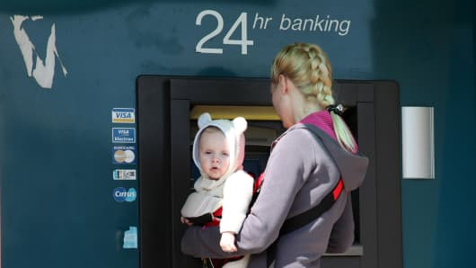 A woman carrying her baby withdraws money at an ATM machine in the Mediterranean city of Limassol.