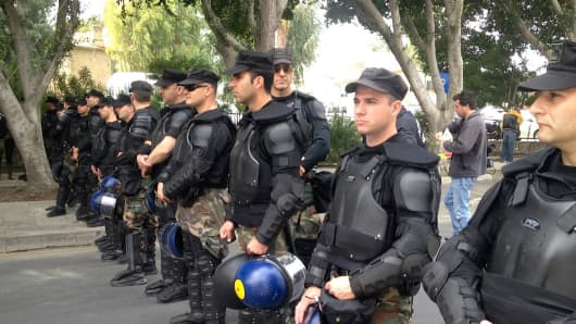 Riot police in Cyprus stand on guard as protesters near by protest the governments handling of the banking crisis.