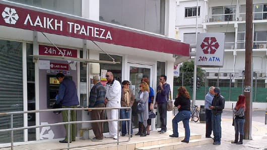 Cypriots line up at a Laiki Bank ATM to withdraw their money.