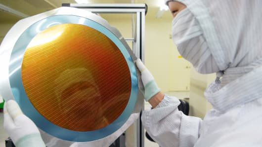 An employee checks a silicon wafer at the production line of Hana Micron Inc.'s plant in Asan, South Korea.