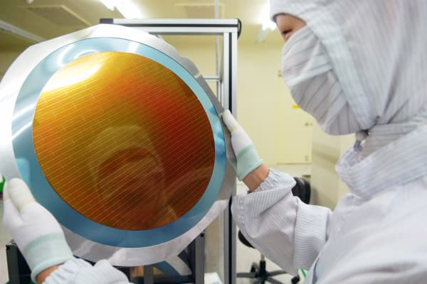 An employee checks a silicon wafer on the production line of Micron's plant in Asia.