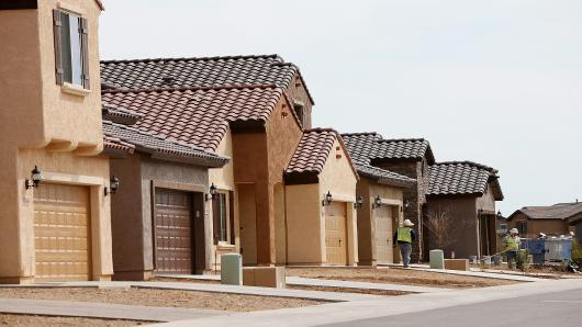Workers stand in front of a row of new homes at the Pulte Homes Fireside at Norterra-Skyline housing development in Phoenix, Arizona