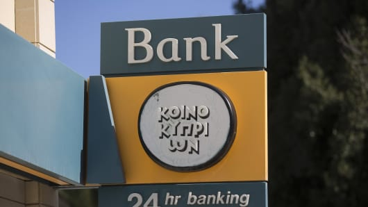 A sign hangs above a Bank of Cyprus Plc branch in Nicosia