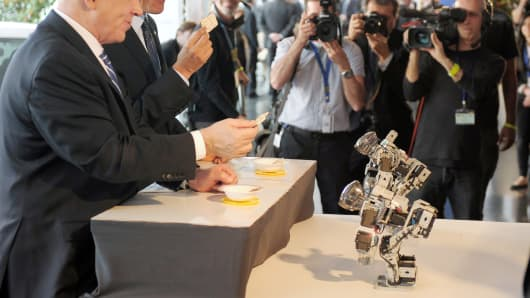 President Barack Obama and Israeli Prime Minister Benjamin Netanyahu sample matza bread offered to them by small robots during a tour of a technology exposition at the Israel Museum in Jerusalem.